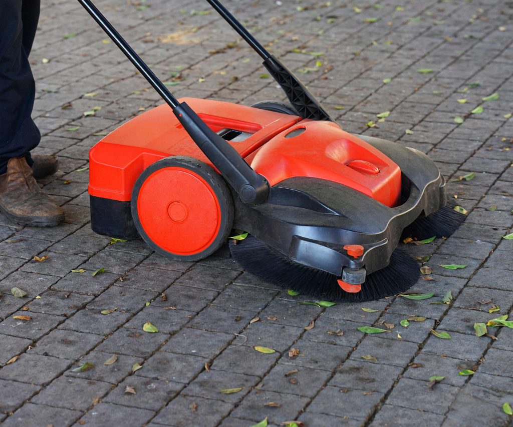 Small walk-behind power sweeper being used outside