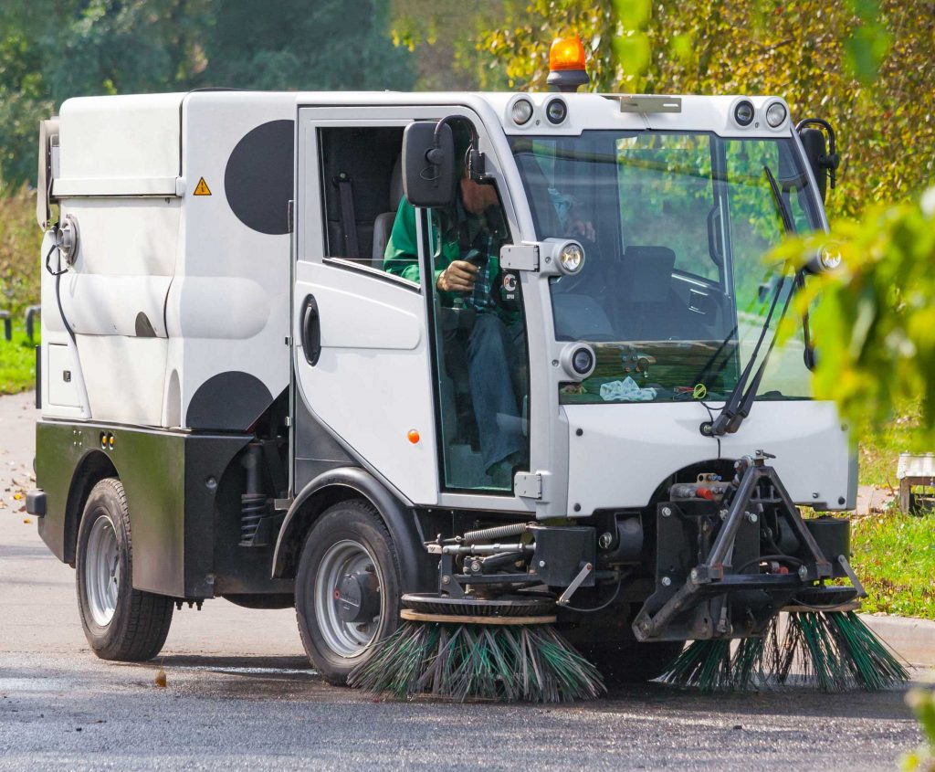 Parking lot sweeper maintaining outdoor lot