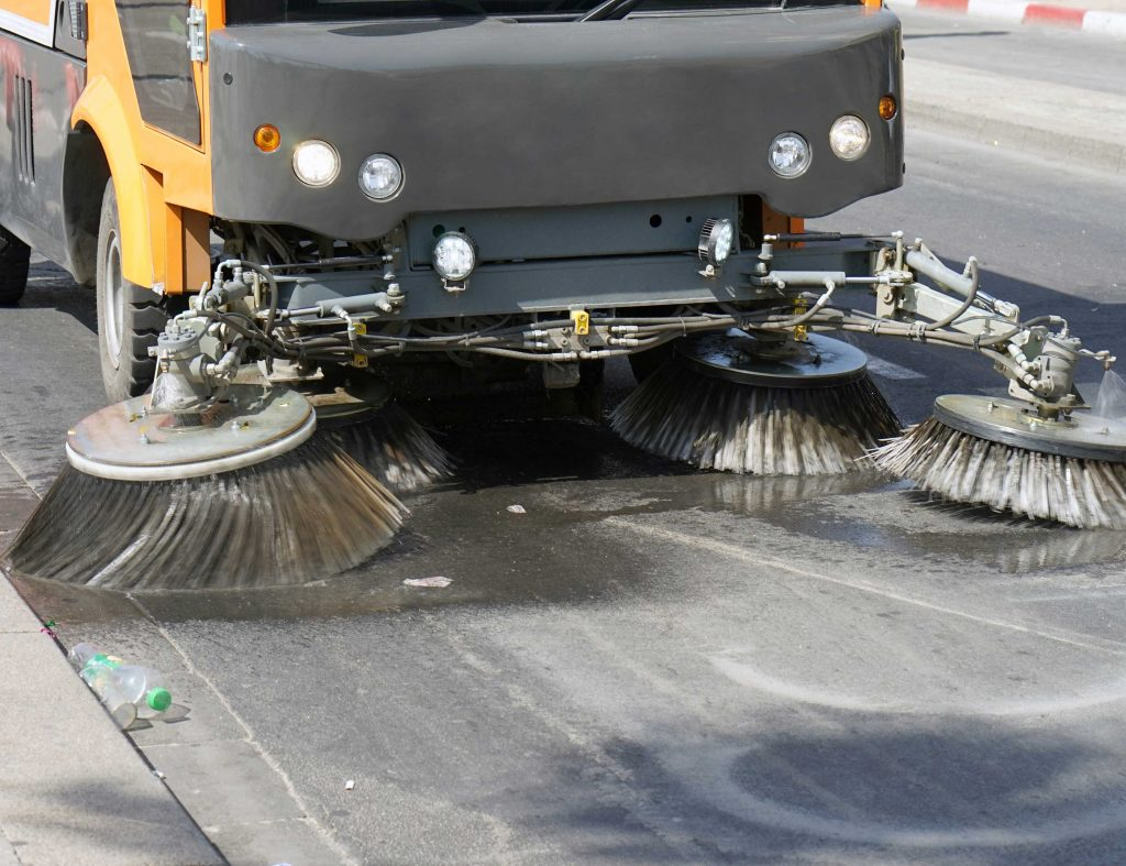 Large used street sweeper cleaning a road outside