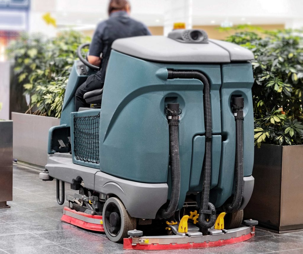 Maintenance worker using a ride-on scrubber machine to clean an indoor facility