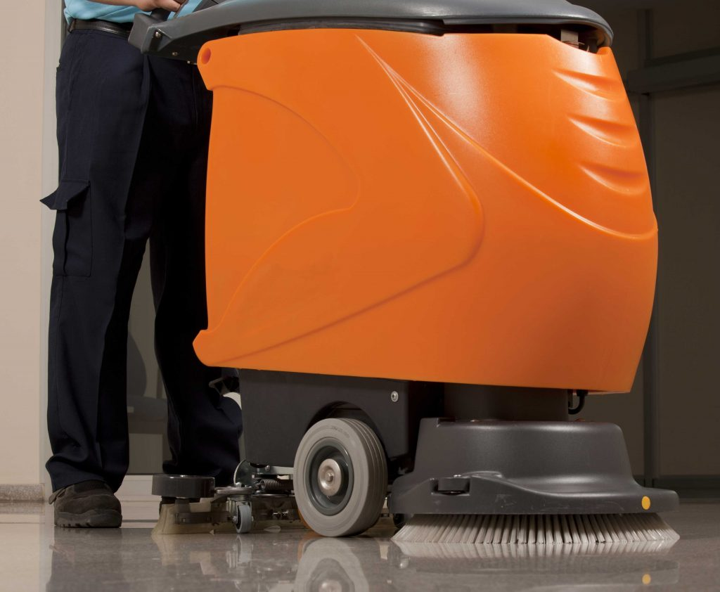 Operator standing with a compact automatic floor scrubber