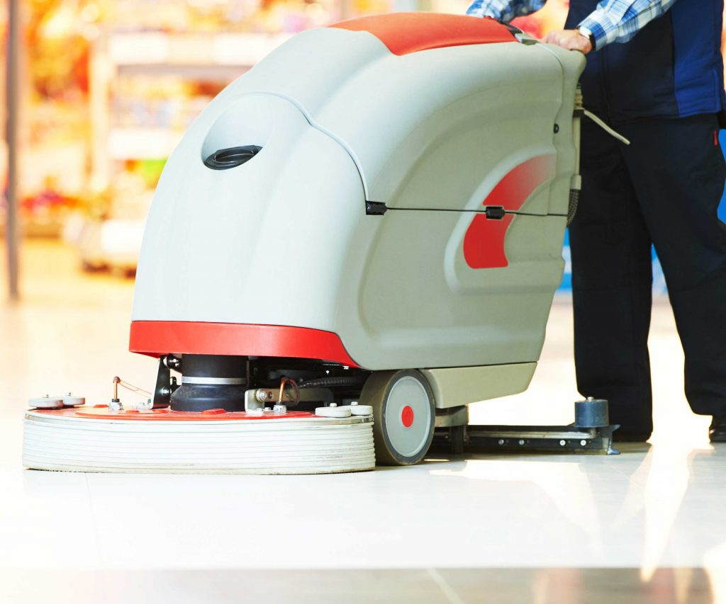White and red walk-behind floor scrubber machine
