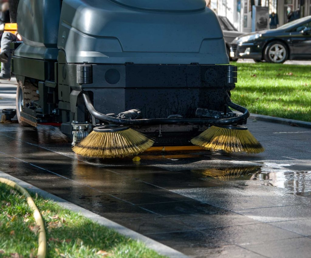 Used ride-on sweeper outside cleaning pavement