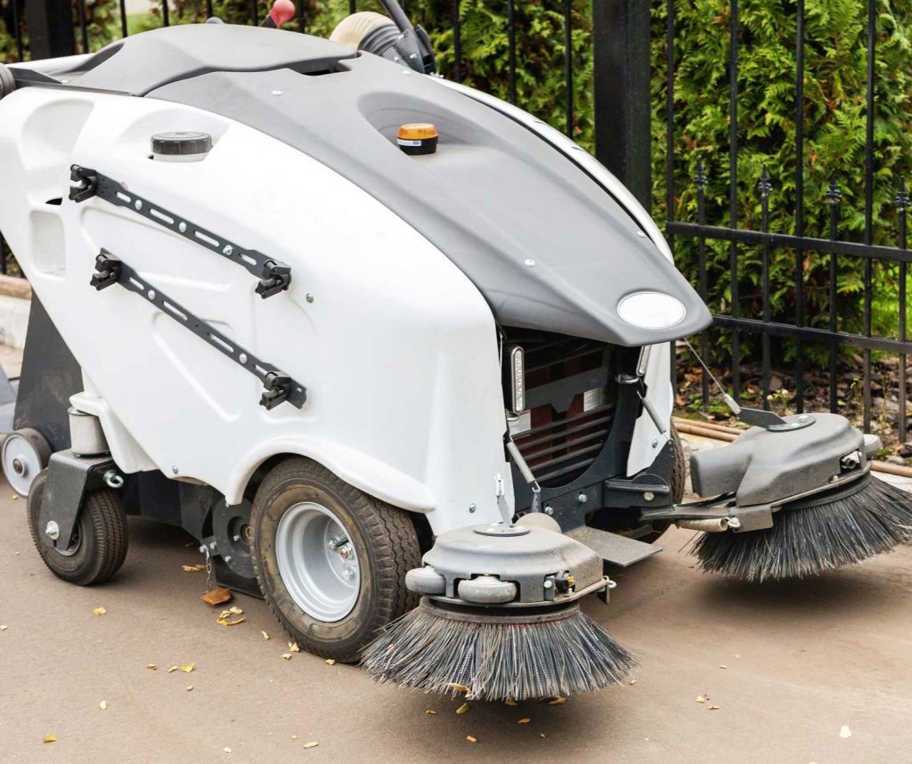 Walk-behind industrial sweeper outside picking up leaves and dirt