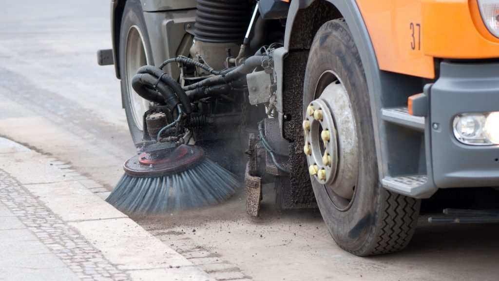 Vacuum sweeper truck cleaning dirt off the pavement