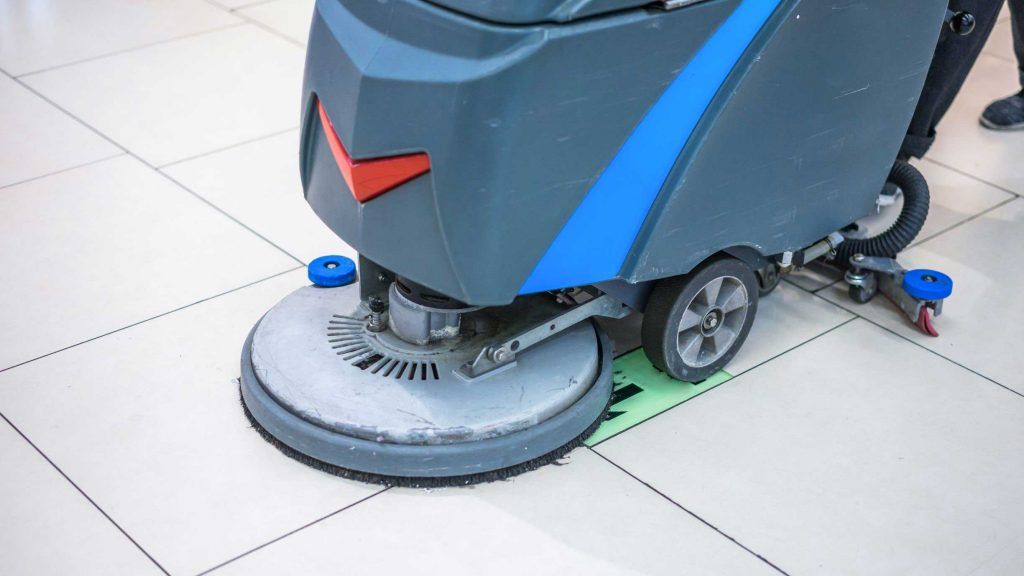 Small industrial floor scrubber cleaning tile flooring