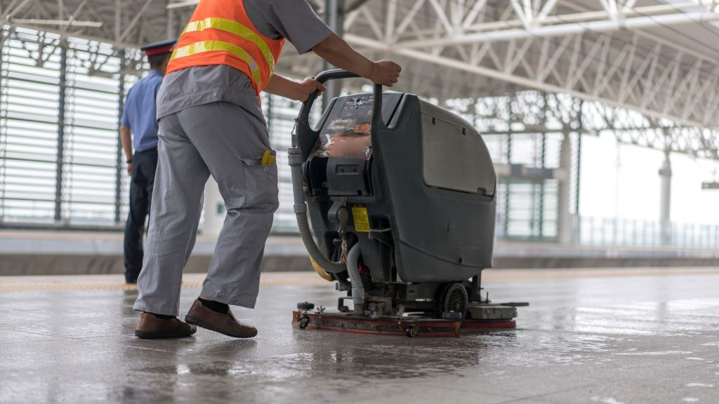 Man using a walk-behind floor scrubber to clean an indoor facility