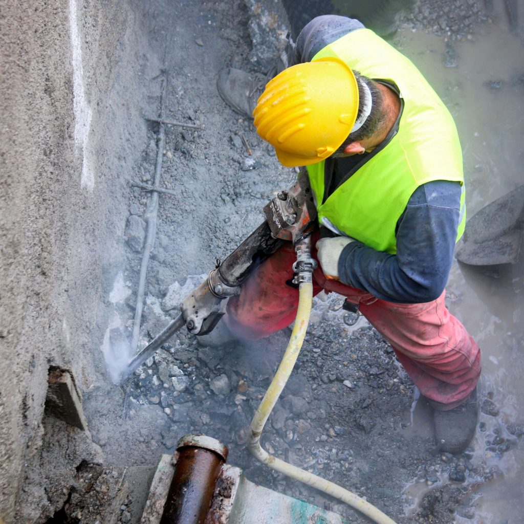 Construction worker in yellow hard hat produces silica dust with a jackhammer