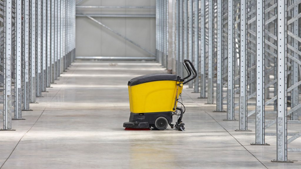 Industrial floor scrubber used in warehouse to eliminate dust