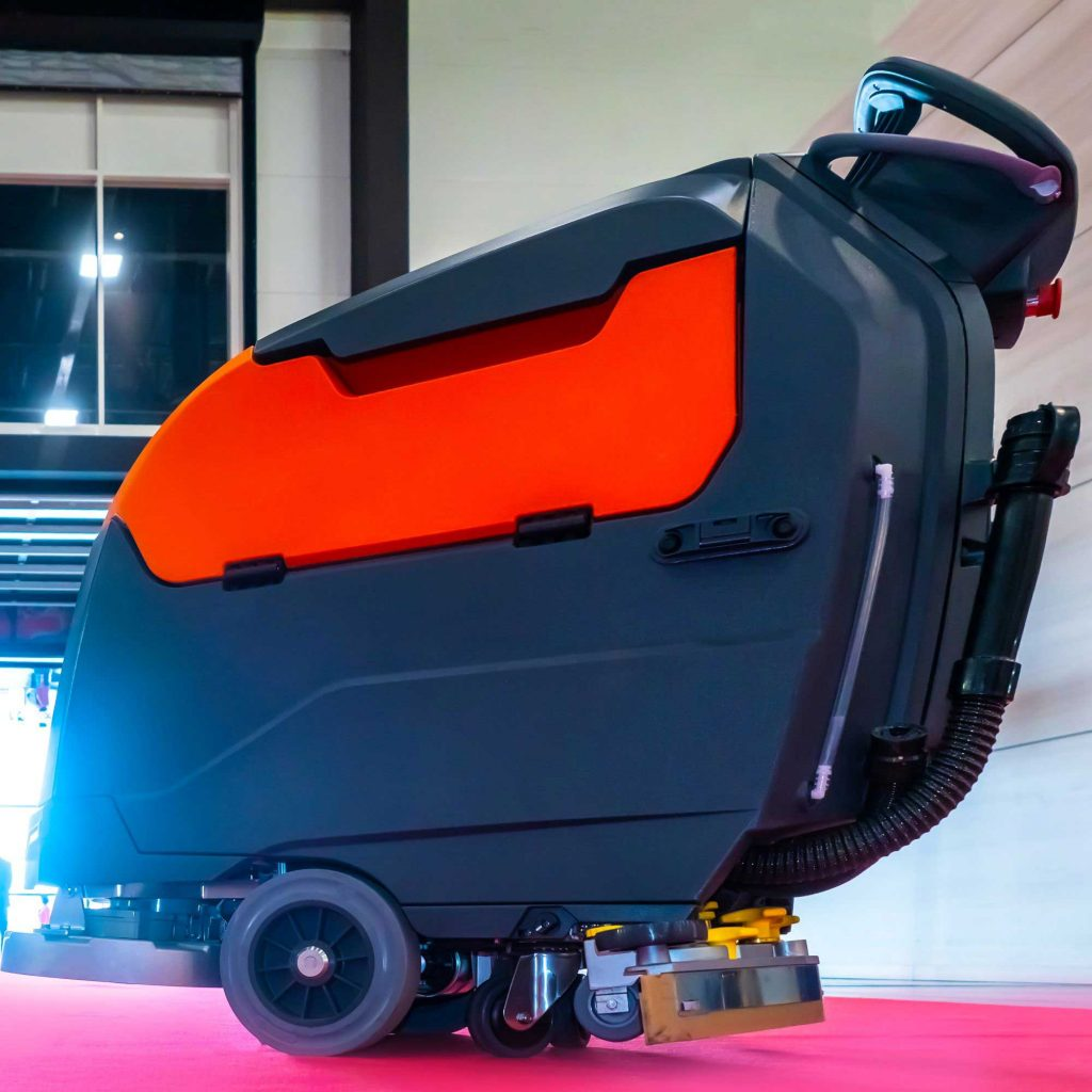 Small walk-behind auto scrubber on red flooring