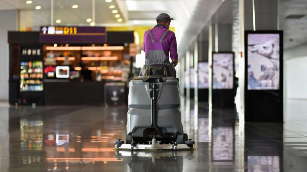 Custodian operating a ride-on auto scrubber in an airport