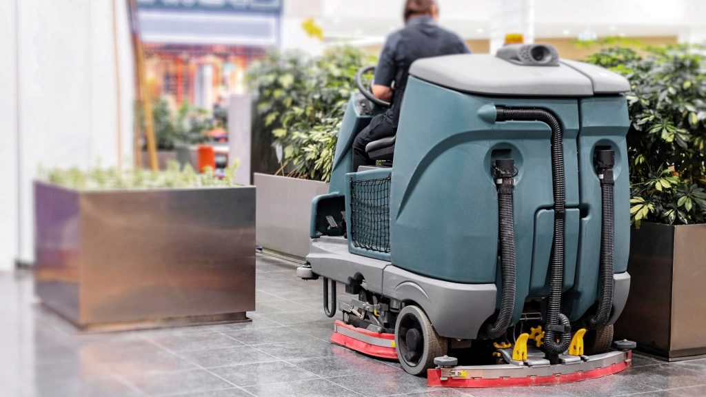 Worker operating a ride-on floor scrubber on tile flooring