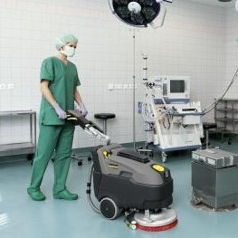 Healthcare worker cleaning hospital floors with a walk-behind floor scrubber