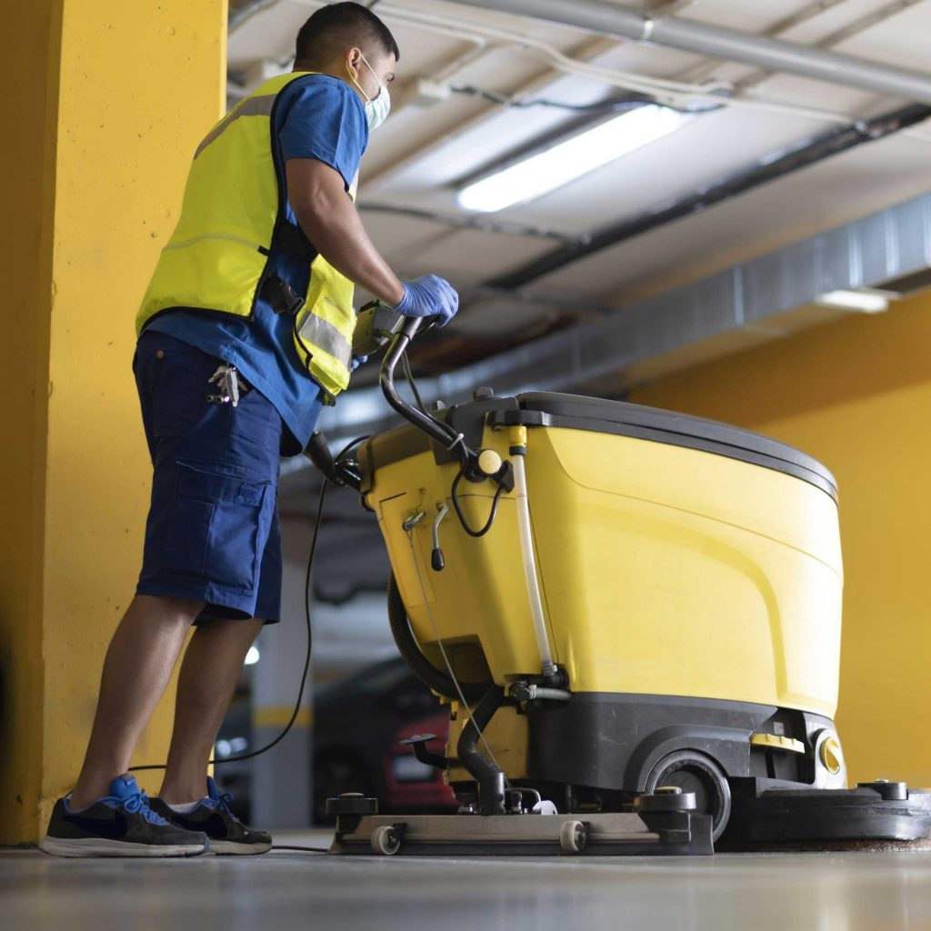Operator in a yellow vest and mask pushing a walk-behind floor scrubber