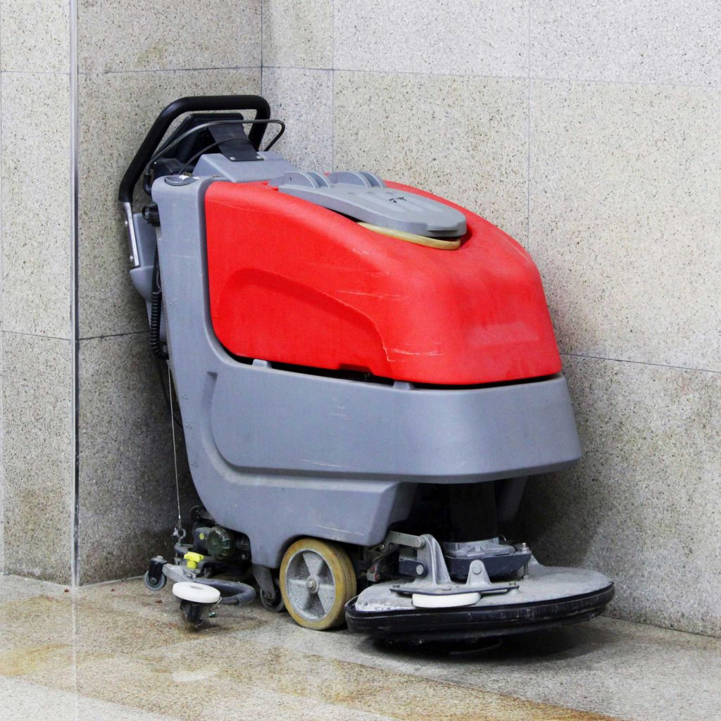 Red and gray walk-behind scrubber used to improve indoor air quality