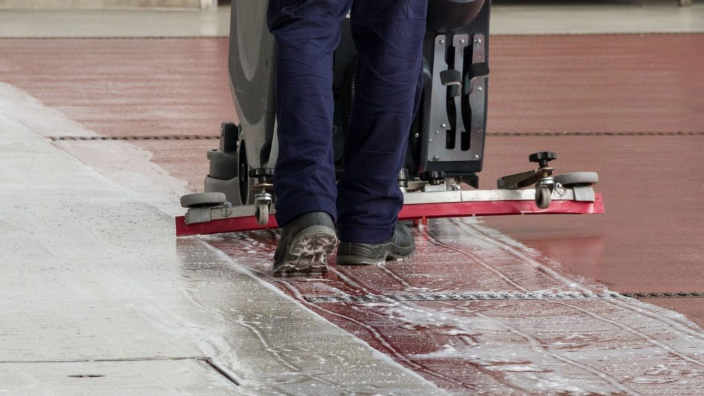 An industrial floor scrubber vacuum not working, that's being operated by a worker.