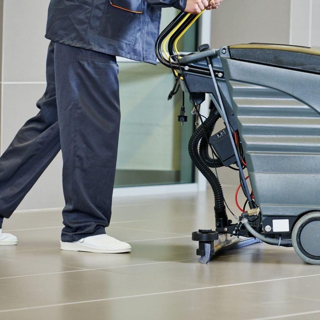 An operator pushing an industrial floor scrubber and its floor scrubber vacuum is not picking up water.