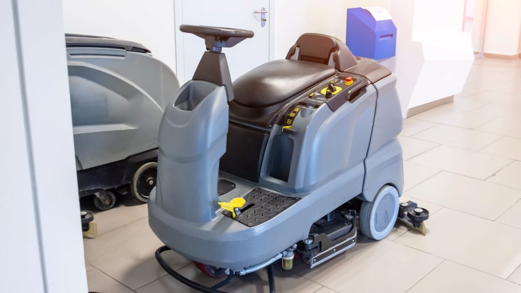 A gray commercial floor scrubber that's next to another gray commercial floor scrubber.