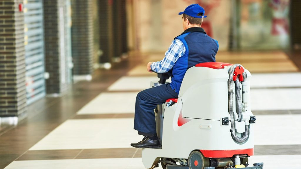 A scrubber operator using their commercial floor machine to practice commercial floor care.