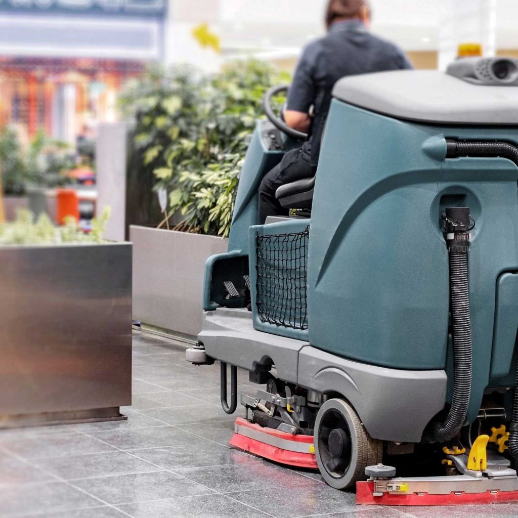 A female operator practicing out-door commercial care with her ride-on floor scrubber.