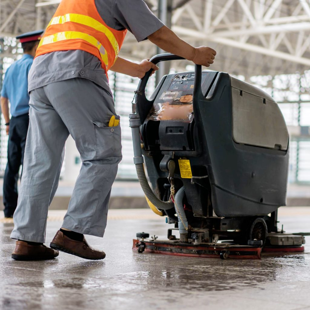 A used ride-on scrubber cleaning an establishment.