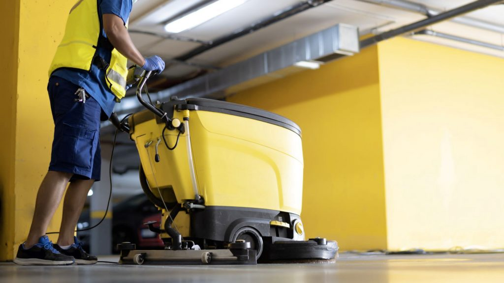 A uniformed man pushing a used walk-behind floor scrubber across a tiled floor.