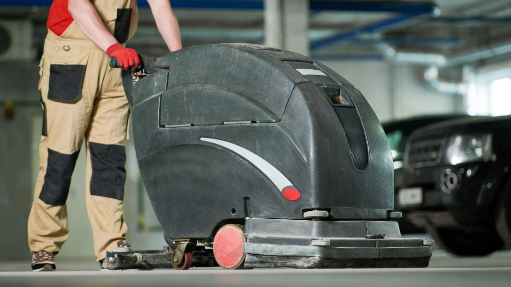 Worker using the best industrial floor scrubber to clean a parking area