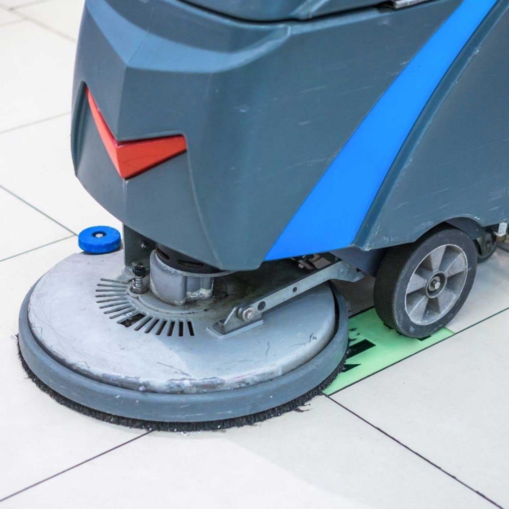 An industrial scrubber cleaning the floor with a scrubber pad
