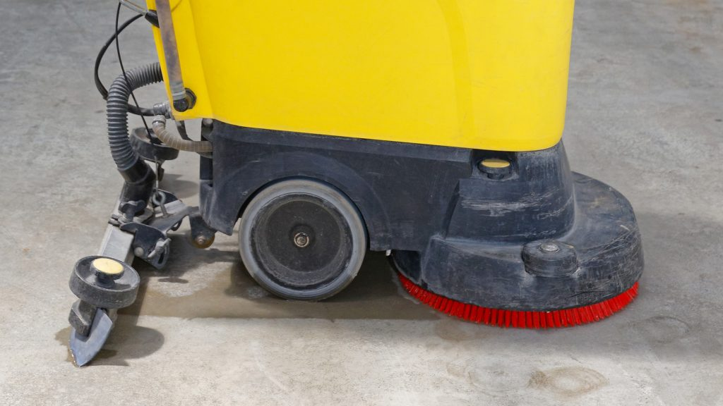 Floor scrubber brushes cleaning a warehouse floor.