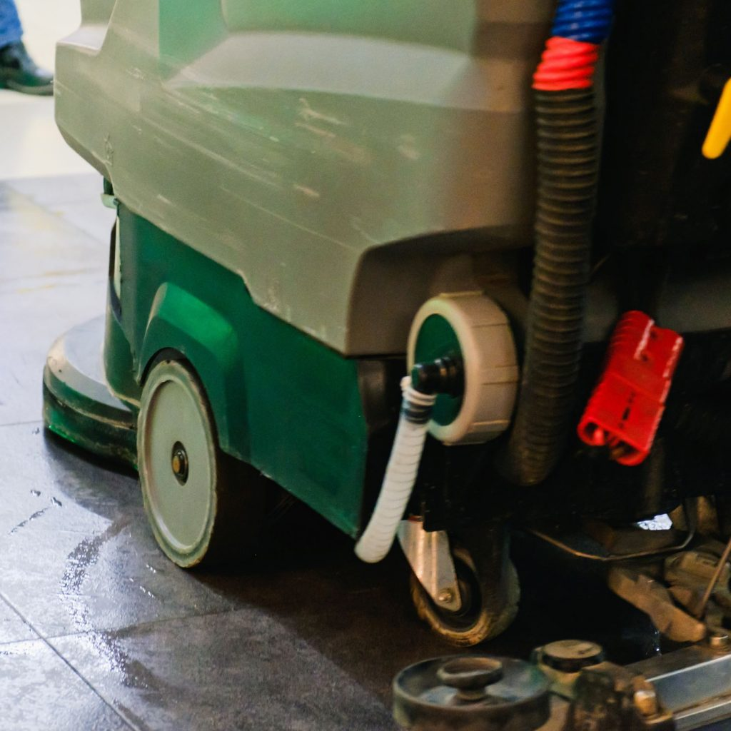 A concrete floor scrubber cleaning a warehouse.