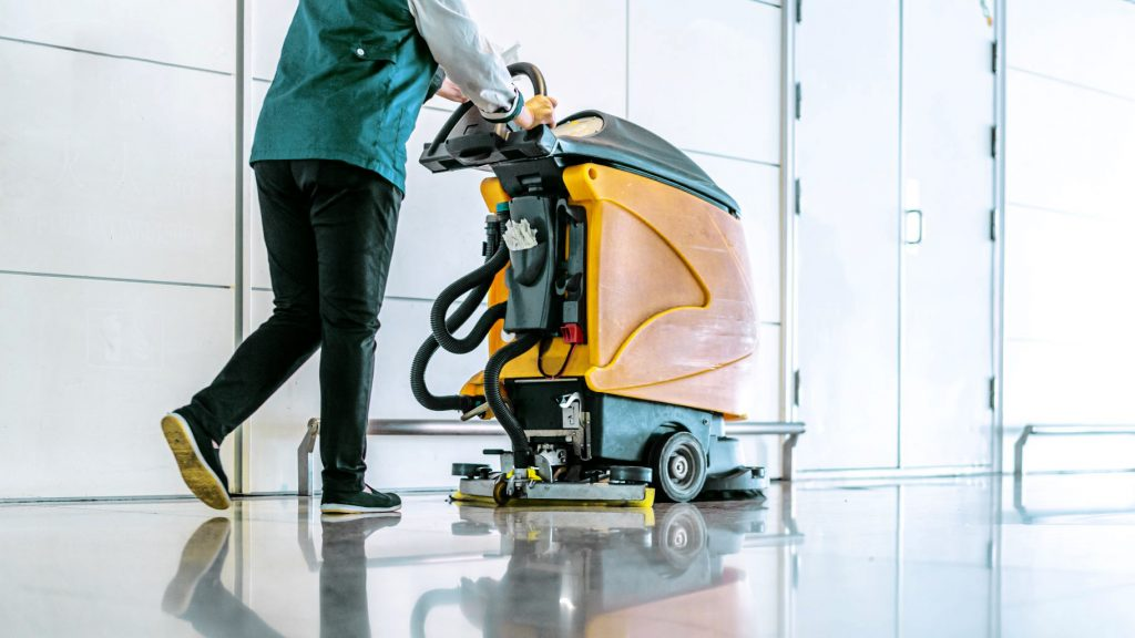 Janitorial staff using an industrial scrubber to clean a floor sustainably