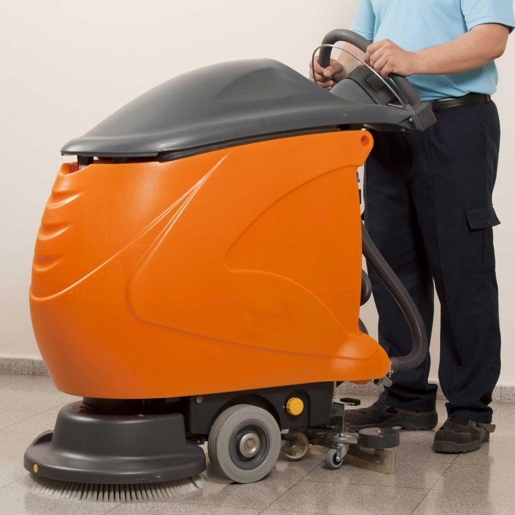 Operator using a walk-behind scrubber