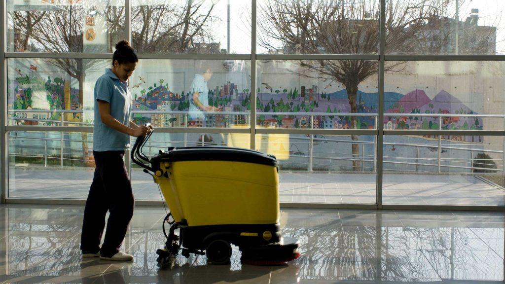 Custodian using floor cleaning pads to scrub industrial flooring