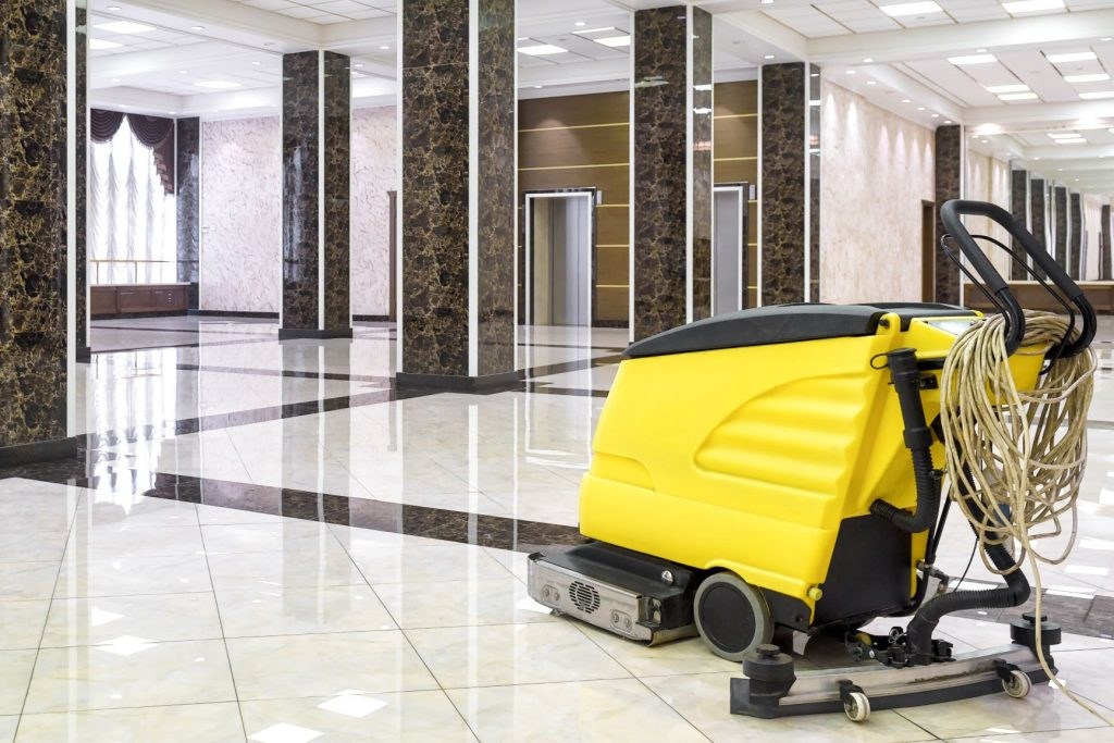 Yellow professional floor cleaning machine in an open hallway